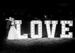 Para młoda całuje się obok napis love
