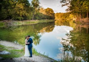 Para młoda przytula sie na tle jesiennego krajobrazu, nad jeziorem