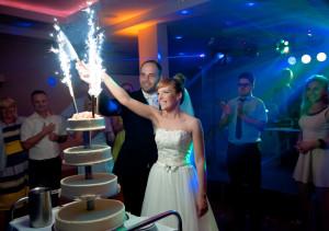 para młoda przy torcie weselnym, kolorowe światła, krojenie torta