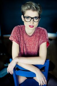 dziewczyna w okularach w czerwonej bluzce siedzi na niebieskim krześle