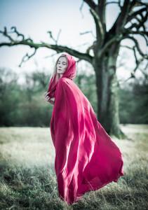 zamyślona postać w pelerynie różowej