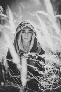 portret zakapturzonej kobiety w trawie