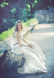 Kobieta w białej sukni siedząca na ławce