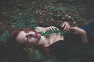 dziewczyna leżąca w lesie na paprociach